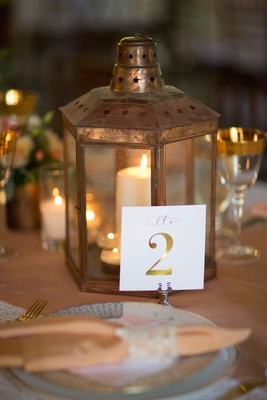 Lantern with candle and white table number with gold calligraphy and gold foil number details rustic