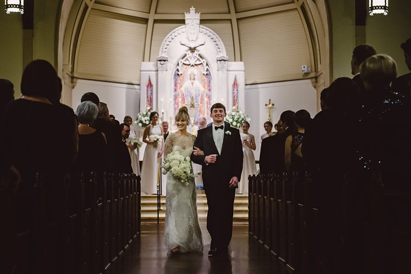 Bride and groom Monique Lhuillier wedding dress walk up aisle at church in North Carolina