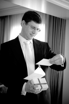 Black and white photo of groom opening bride's present