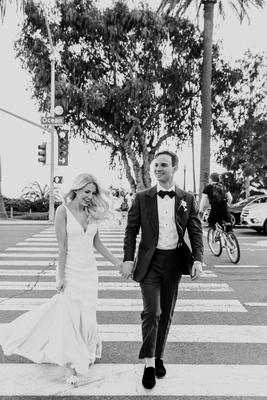 black and white photo of bride and groom crossing ocean avenue in santa monica california