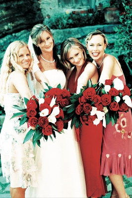Bridesmaids carry red rose and white calla lily bouquets