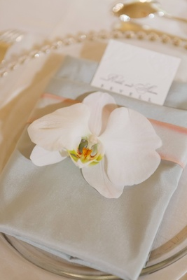 Folded dinner napkins with orchid place topper