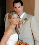 Bride and groom in summer attire with orange flowers