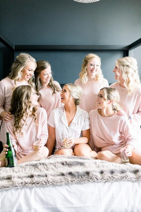 bride and bridesmaids getting ready in matching pajamas with glasses of champagne