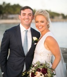 Bride in sleeveless wedding dress with fall theme bouquet groom in suit with light blue tie on beach