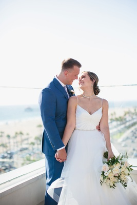 bride in v neck spaghetti strap wedding dress groom in blue suit on balcony overlooking beach ocean