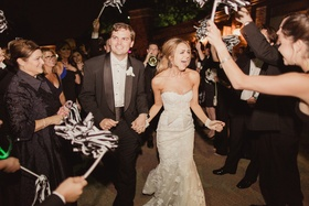 bride in mira zwillinger wedding dress, groom in tux, grand exit with black and white pom-poms