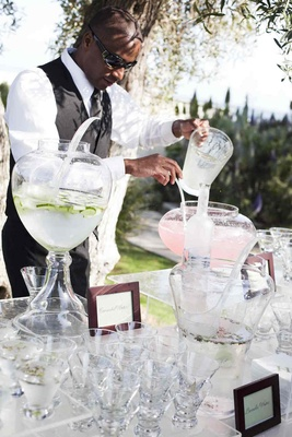 African American server pours pitcher into water urn