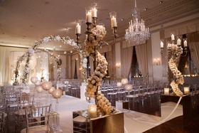 Ivory floral, gold candelabras and floral arches create an elegant wedding aisle.