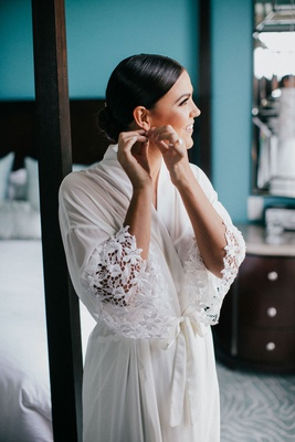 bride with slick hairstyle low bun putting on earrings white robe lace flower motif sleeves