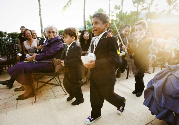 Three ring bearers walk down aisle with pillow and broom