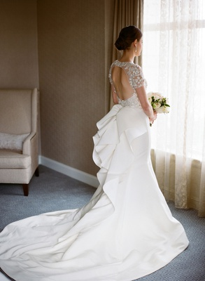 Bride looking out window back of dress marchesa keyhole back bow detail in back
