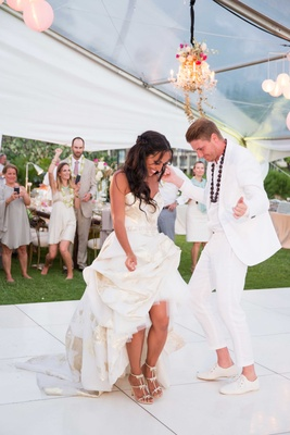 Bride in high low reception dress with groom in white suit for destination wedding dancing in tent