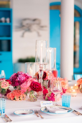 destination wedding in capri, italy, with bright pink flowers and bright blue glasses and chairs