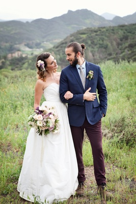 Bride in a strapless ball gown and groom with mun man bun in blue blazer, brown pants