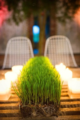 Wedding reception decor of a strip of wheatgrass surrounded by candles