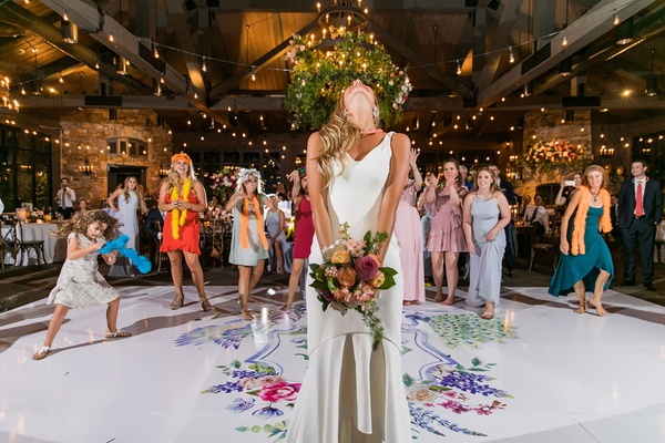 wedding reception bouquet toss tradition on custom white dance floor colorful wedding crest