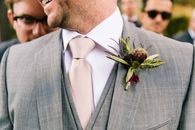 groom's rustic boutonniere featuring green and deep purple to match wine color scheme