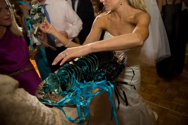 bride passes out blue and green masquerade masks