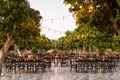 dark wood tables and chairs with trees, bistro lights, courtyard wedding reception