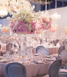Wedding reception white drapery pink linen flower centerpieces silver chairs tall flower chandelier