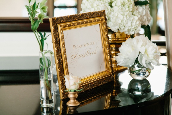 Gold ornate picture frame with please sign our guestbook sign on table