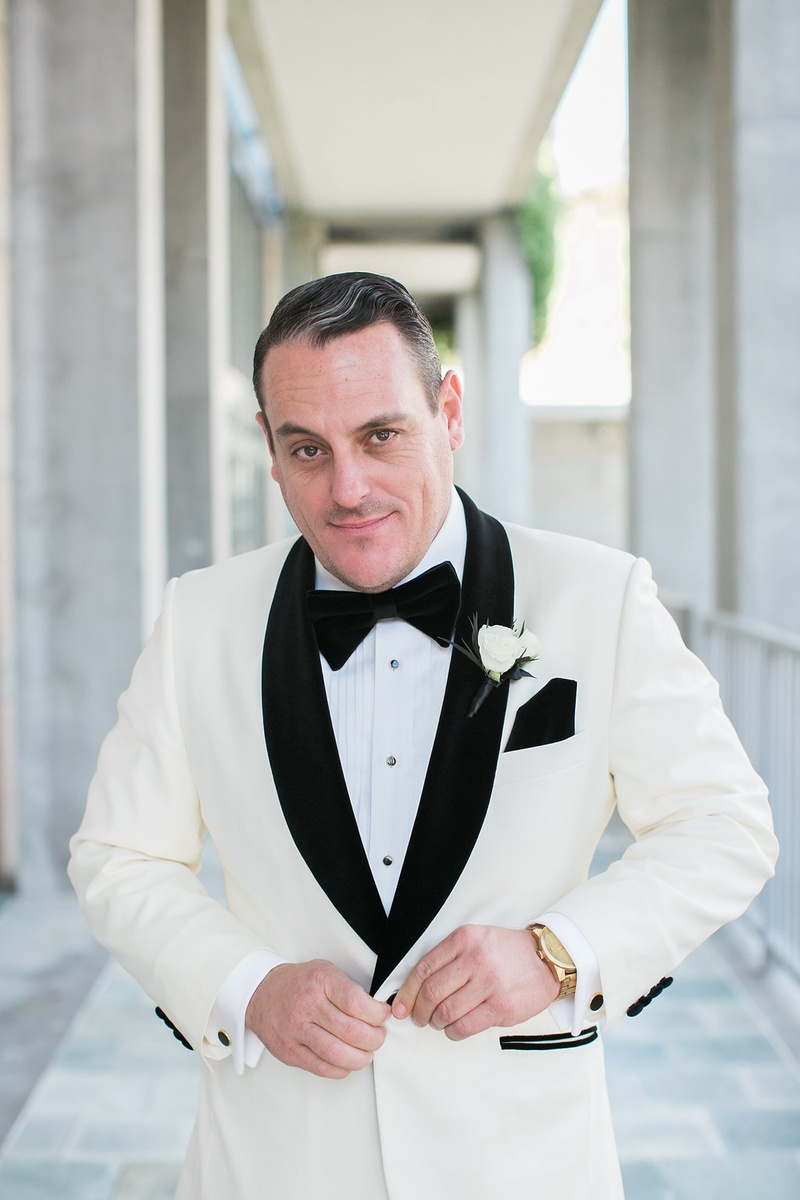 groom in white tuxedo jacket with black lapels and black pocket square