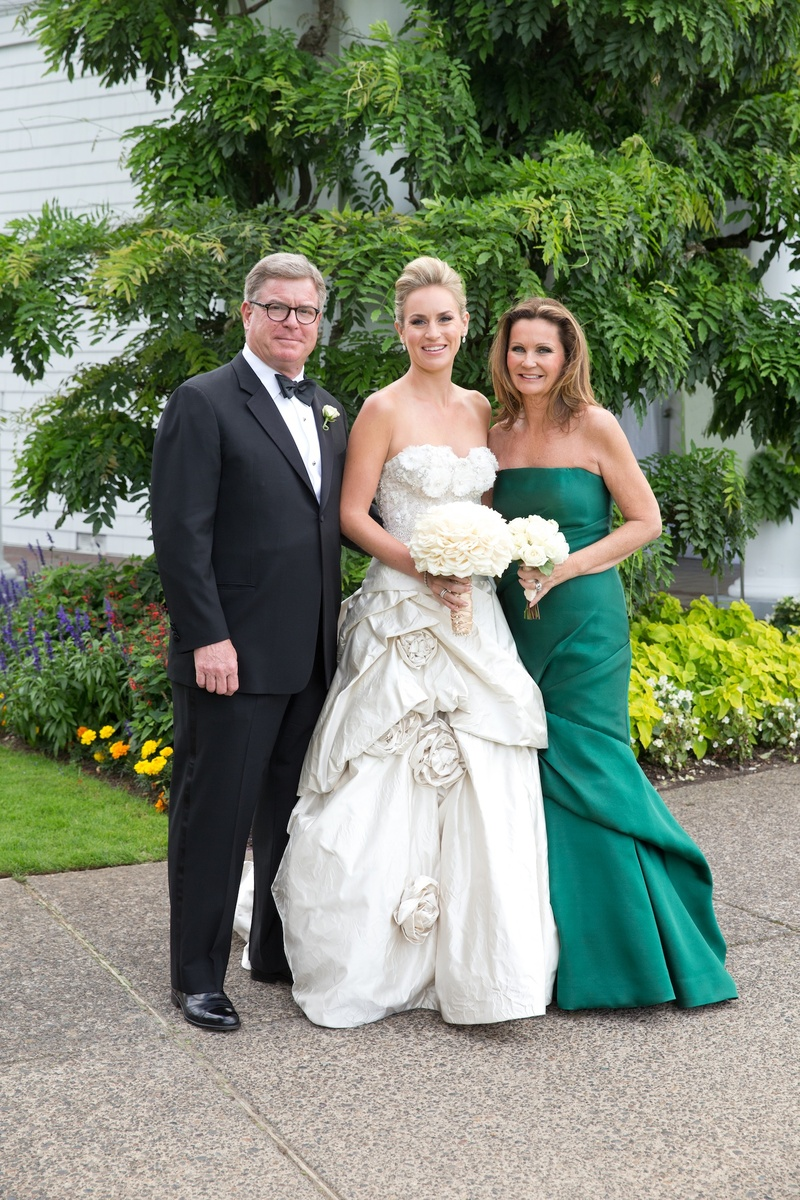 Bride with father and mother of bride in green dress