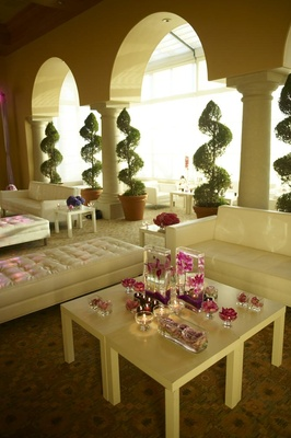 White lounge furniture with purple flower centerpieces