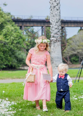 flower girl in pink dress with flower sash belt basket flower crown ring bearer in vest pink bow tie