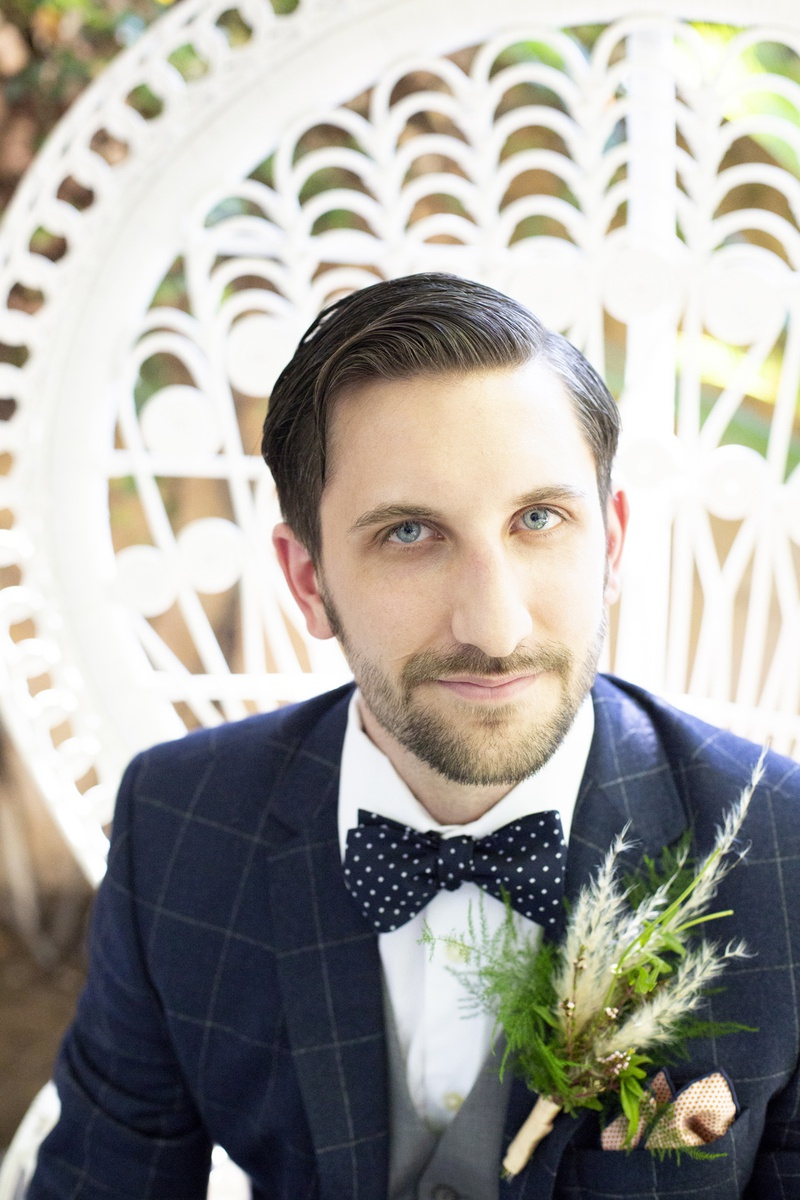 large boutonniere with fern and pampas grass, navy windowpane suit, polka dot tie