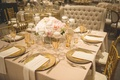 Wedding reception table with gold chargers, flatware, stemware, tan napkins, tablecloth