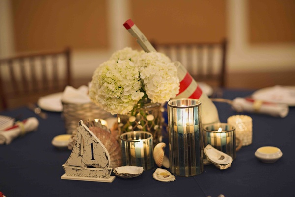 Wood buoy and sailboat centerpiece at rehearsal dinner