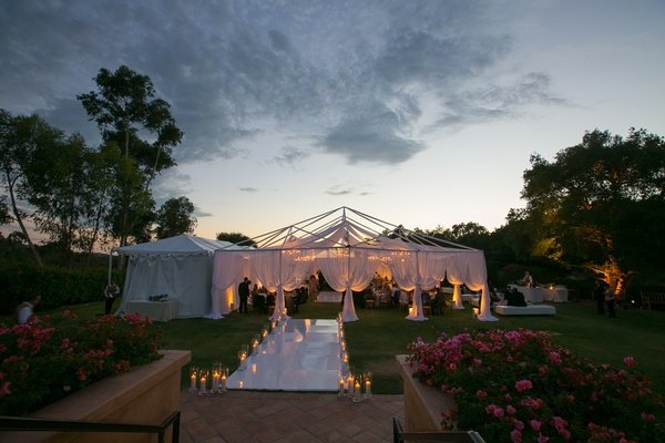 walkway filled with candles welcomed guests inside the tent