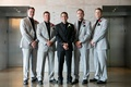 groom in all black ensemble with white boutonniere standing groomsmen in grey black pink boutonniere