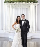 bride in oscar de la renta, groom in j. hilburn under chuppah of flowers and ribbons