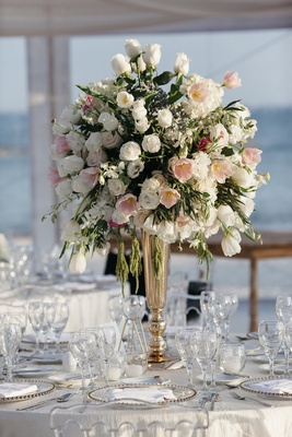 Tented wedding reception with tall centerpiece of white roses, orchids, hydrangeas, pink tulips