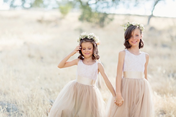 Two flower girls holding hands in tan neutral wedding looks tank dresses