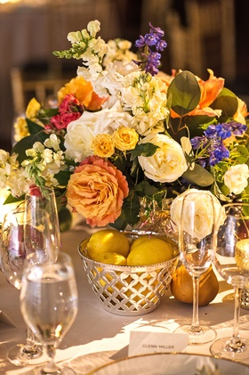 Wedding reception low centerpiece with basket filled with lemon pears orange and yellow flowers