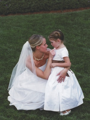 Bride kneeling down with little flower girl