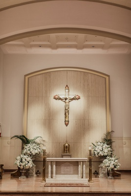 wedding ceremony at church in dallas cross altar greenery white flower arrangements urns