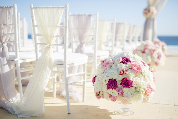 Beach wedding ceremony sheer fabric on back of chair small flower arrangements round rose designs
