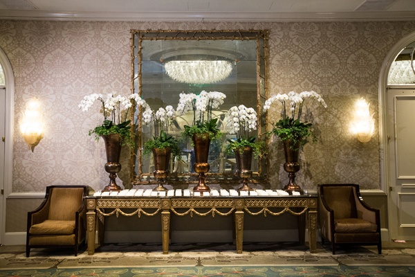 five bronze vases with white orchids at escort card table