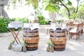 Barrels with infused water station and pineapples as decor for hawaiian wedding