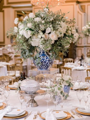 wedding reception centerpiece white flower greenery blue white vase acrylic riser gold details