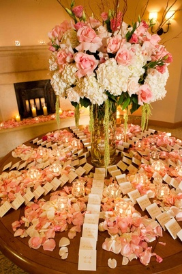 Seating cards on round table covered in petals