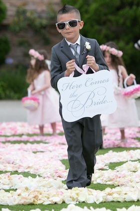 Ring bearer in grey suit holding die-cut Here Comes the Bride sign