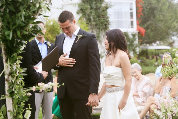 groom in armani emotional while exchanging vows with bride in monique lhuillier crop top gown
