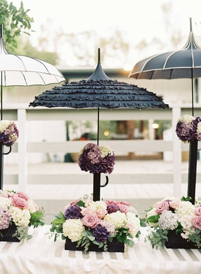 French theme wedding decor with black and white parasol umbrellas with boxes of flowers