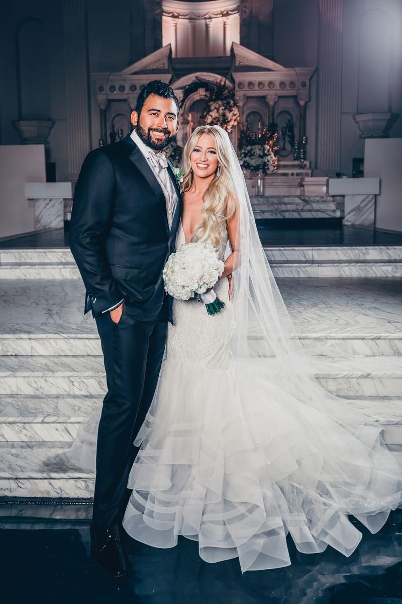 bride in lazaro mermaid wedding dress long blonde hair veil white bouquet with groom in suit white